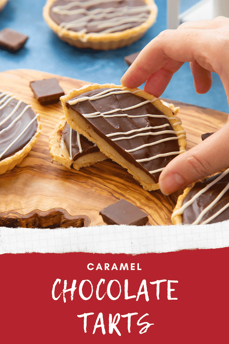 Mini chocolate tarts on an olive board. One tart has been cut in half. A hand reaches for a half. Caption reads: caramel chocolate tarts