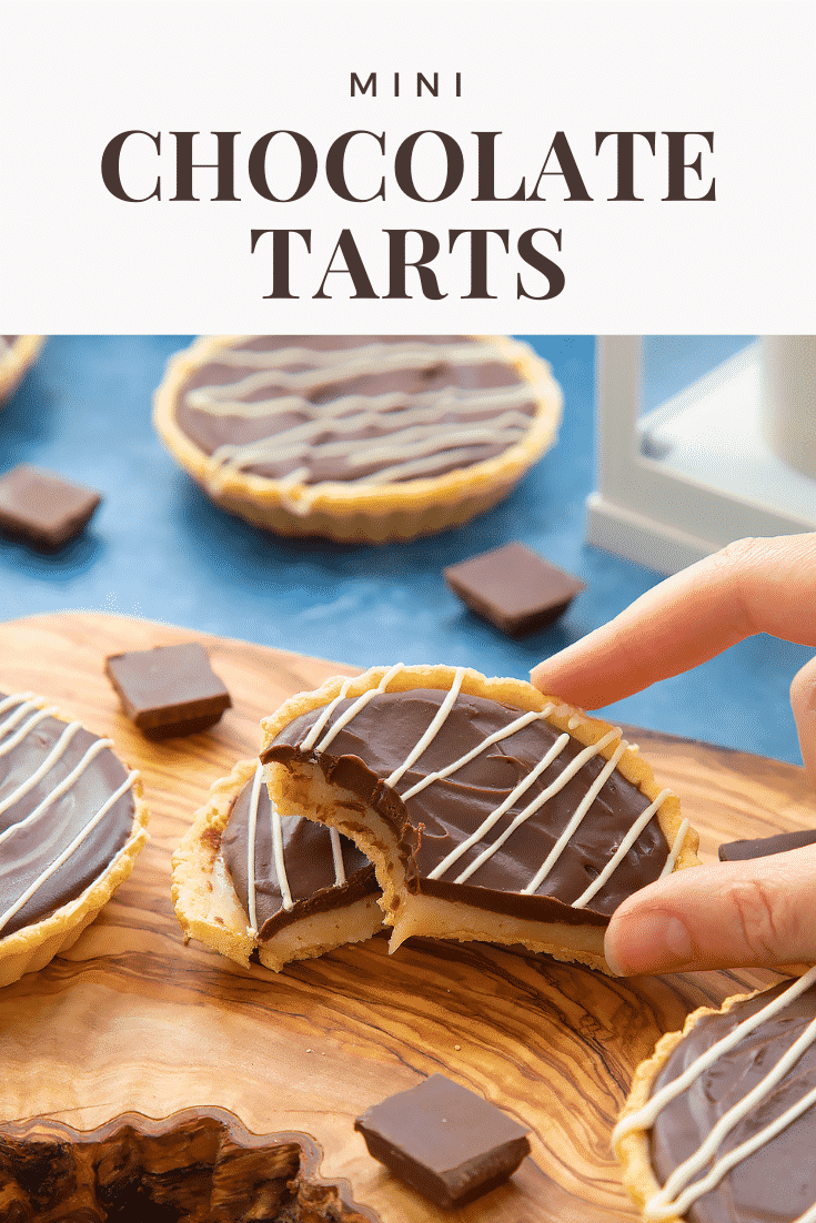Mini chocolate tarts on an olive board. One tart has been cut in half. A hand holds a half, which has a bite out of it. Caption reads: mini chocolate tarts