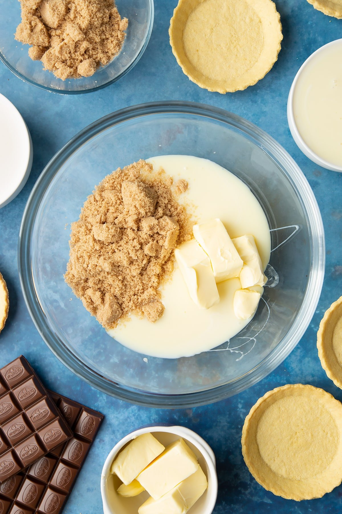 Light brown sugar, butter and condensed milk in a large mixing bowl. Ingredients to make mini chocolate tarts surround the bowl.
