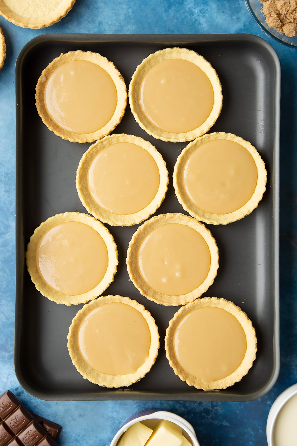 Small pastry cases filled with caramel on a large metal baking tray. Ingredients to make mini chocolate tarts surround the tray.