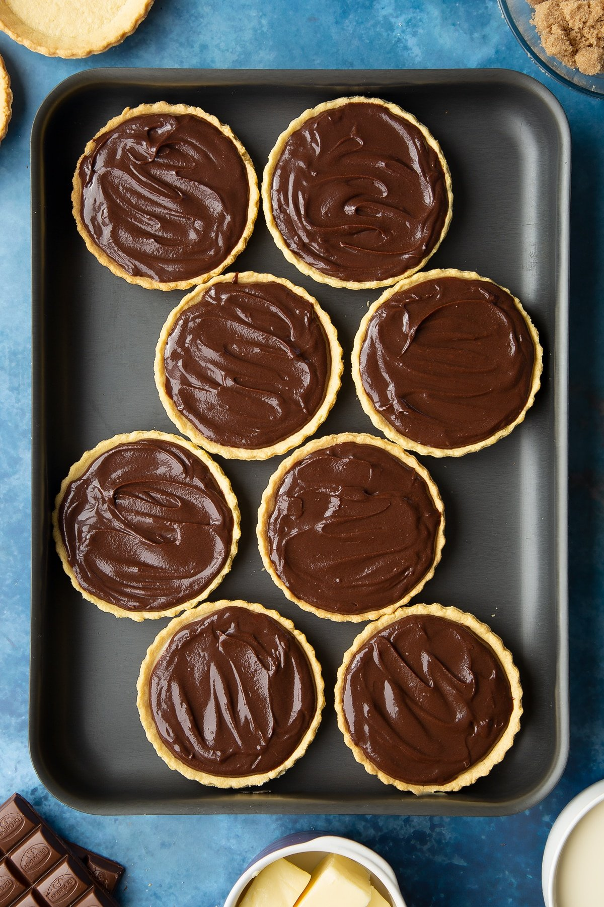 Mini chocolate tarts filed with caramel and chocolate ganache on a large metal tray.