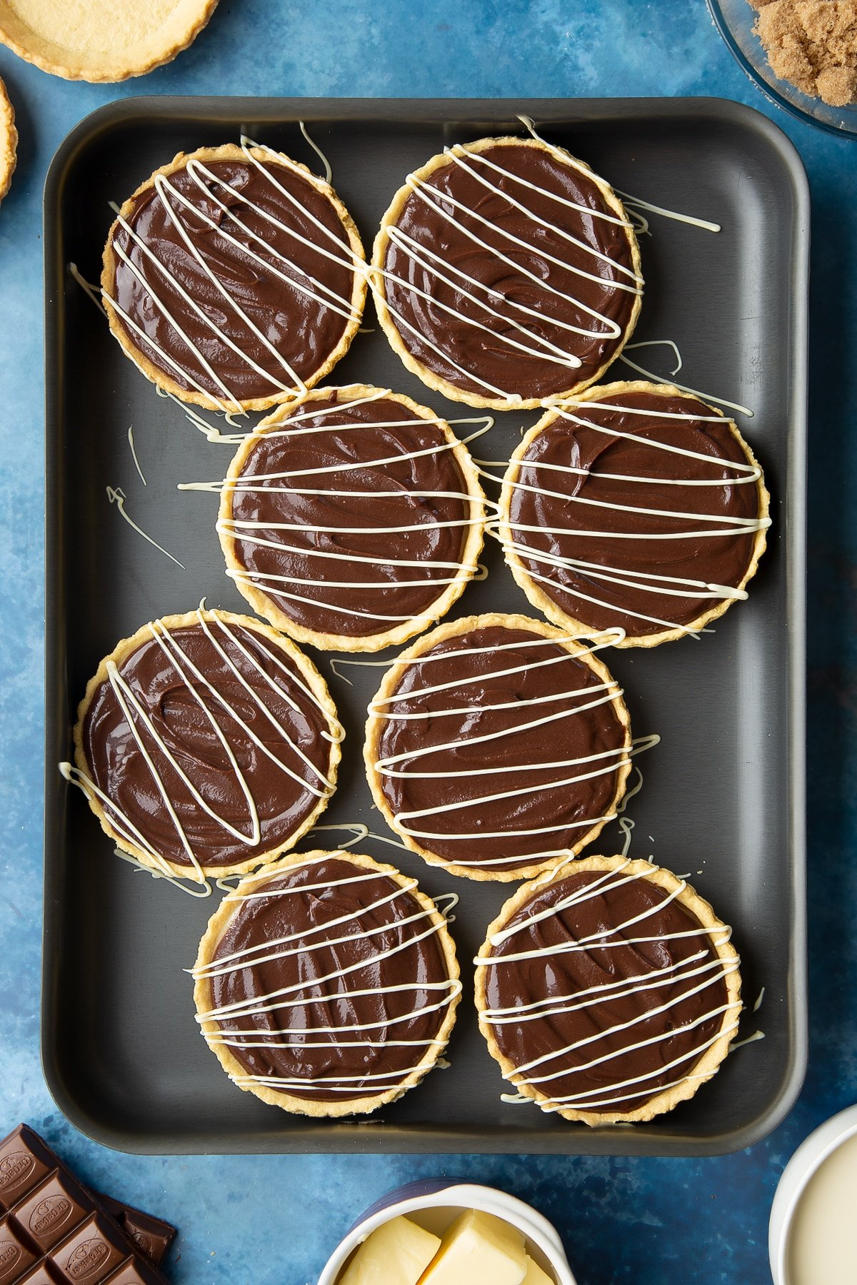 Mini chocolate tarts decorated with drizzled white chocolate on a large metal tray.