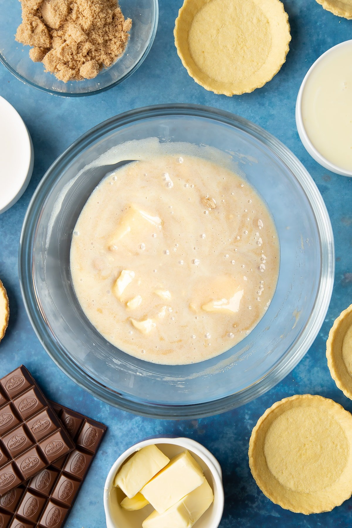 Light brown sugar, butter and condensed milk stirred together in a large mixing bowl. Ingredients to make mini chocolate tarts surround the bowl.