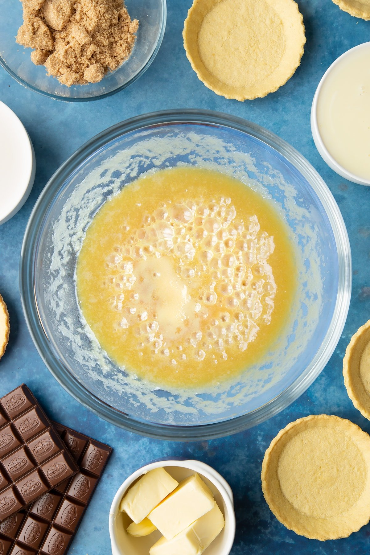 Light brown sugar, butter and condensed milk heated together in a large mixing bowl. Ingredients to make mini chocolate tarts surround the bowl.