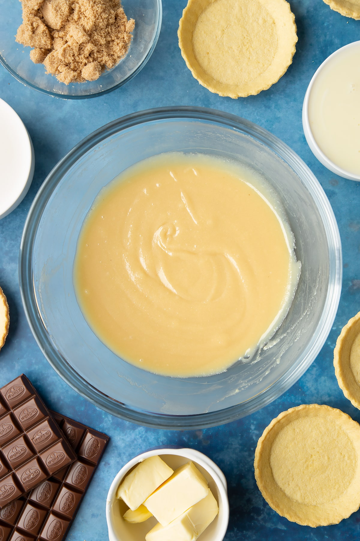 Freshly made caramel in a large mixing bowl. Ingredients to make mini chocolate tarts surround the bowl.