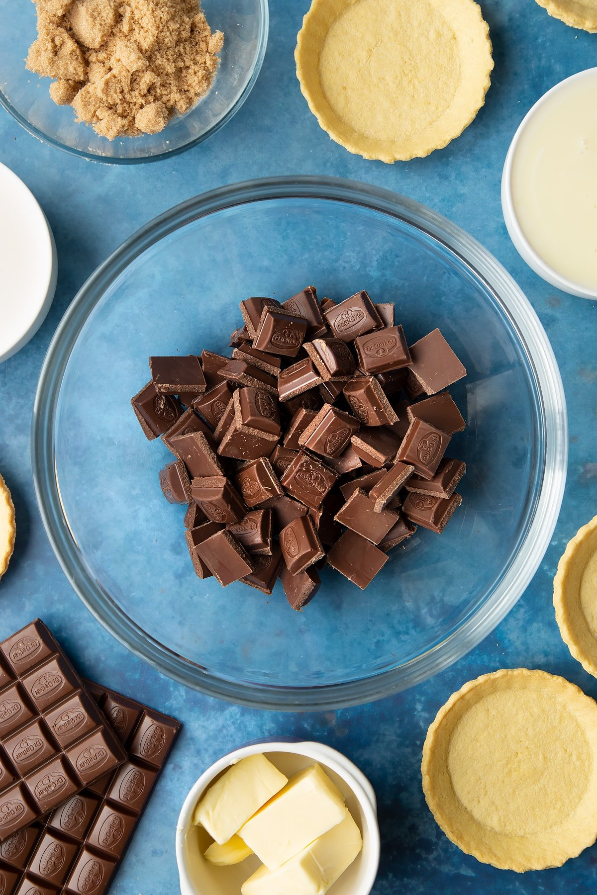 Broken up milk chocolate in a large mixing bowl. Ingredients to make mini chocolate tarts surround the bowl.