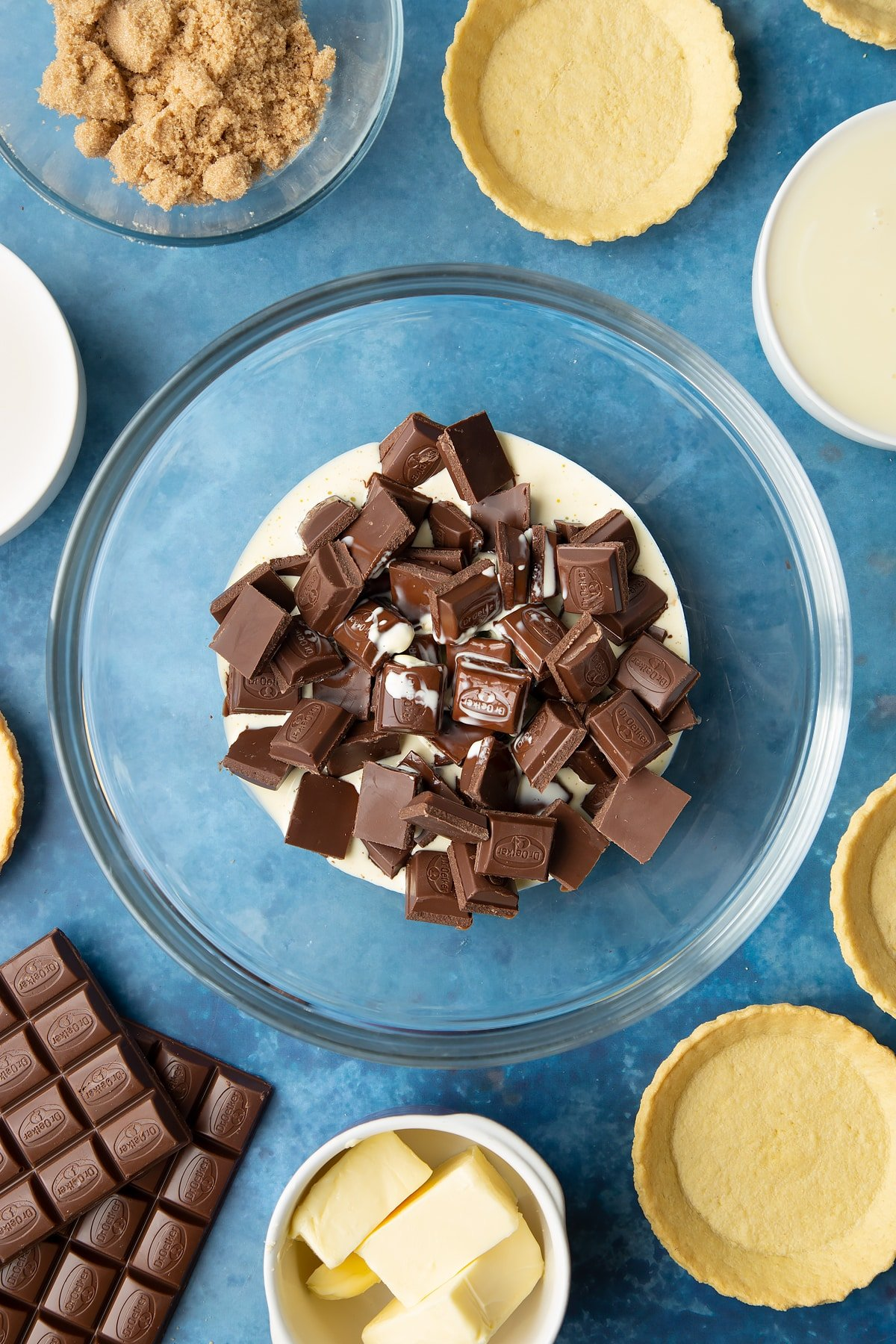 Broken up milk chocolate and heated cream in a large mixing bowl. Ingredients to make mini chocolate tarts surround the bowl.