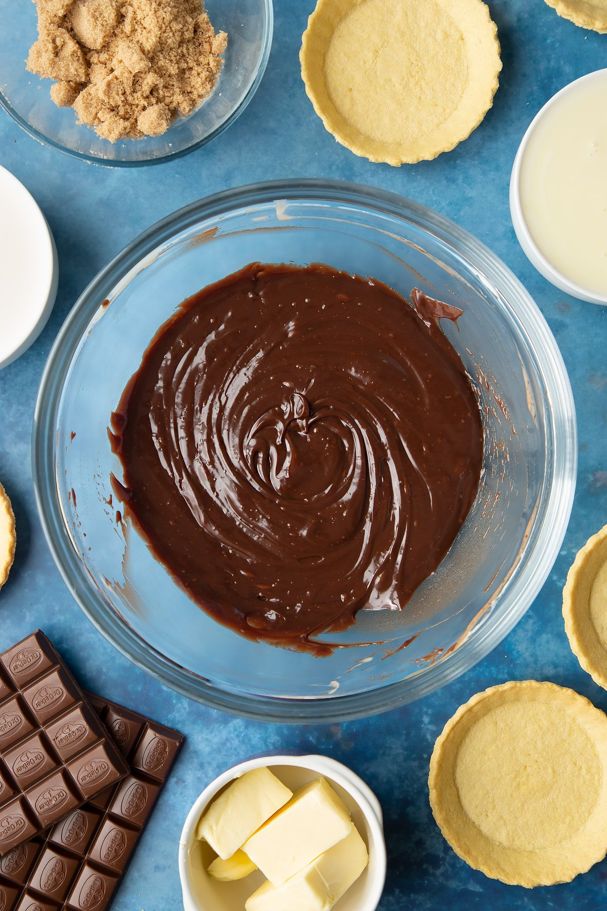 Freshly made milk chocolate ganache in a large mixing bowl. Ingredients to make mini chocolate tarts surround the bowl.