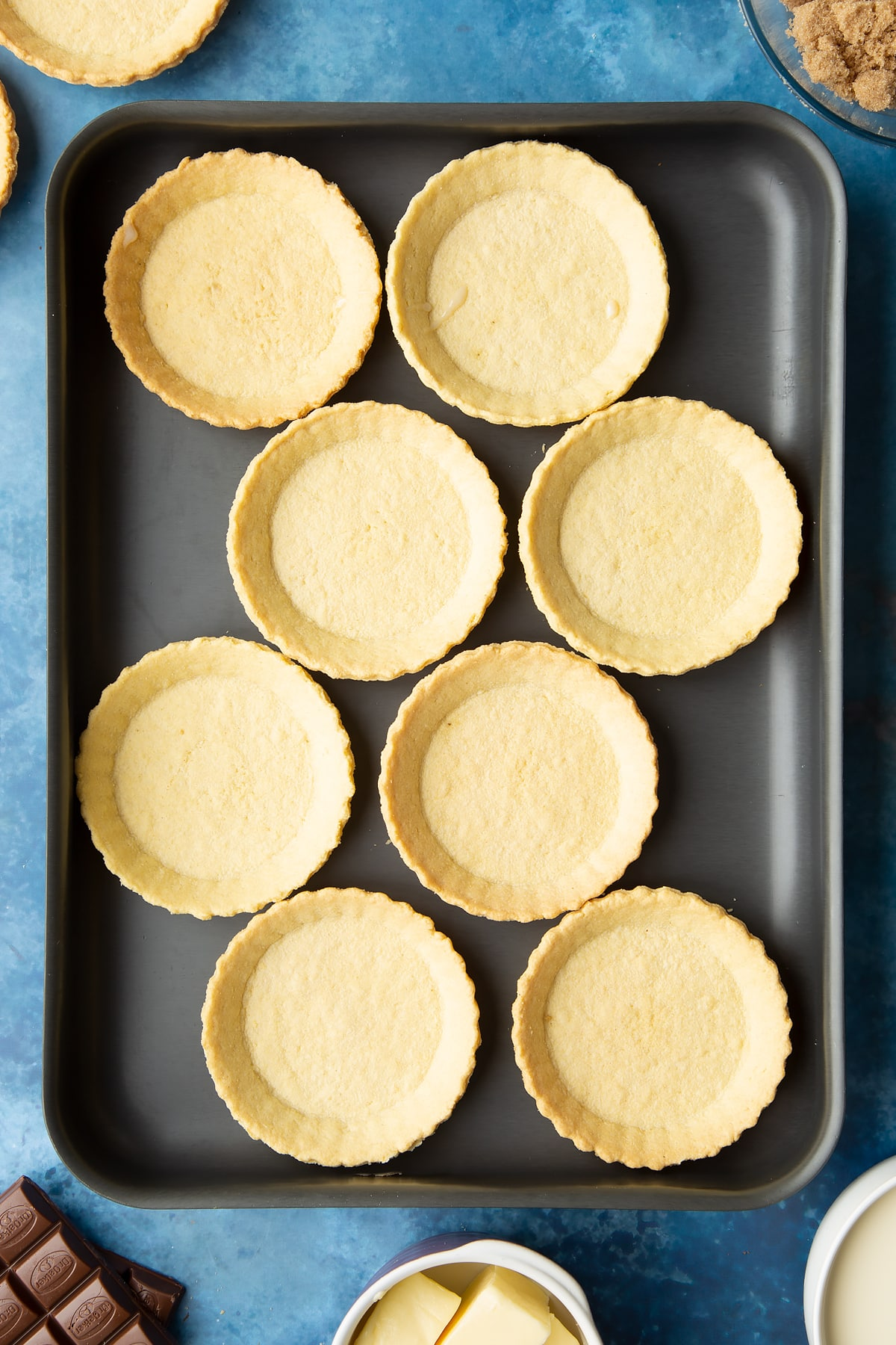Small pastry cases on a large metal baking tray. Ingredients to make mini chocolate tarts surround the tray.