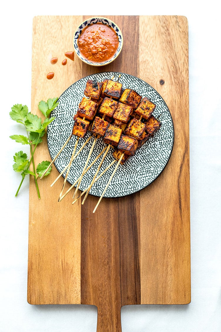 A pile of orange chipotle tofu skewers sit on top of a wooden chopping board on a white background.