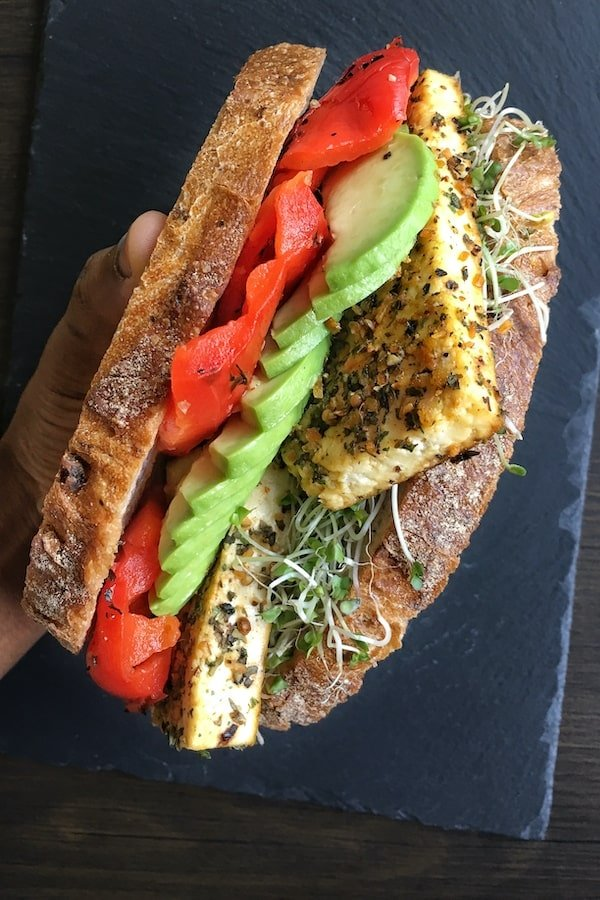 Crusty bread slices stacked between tofu, avocado and roasted red peppers held together with a hand.