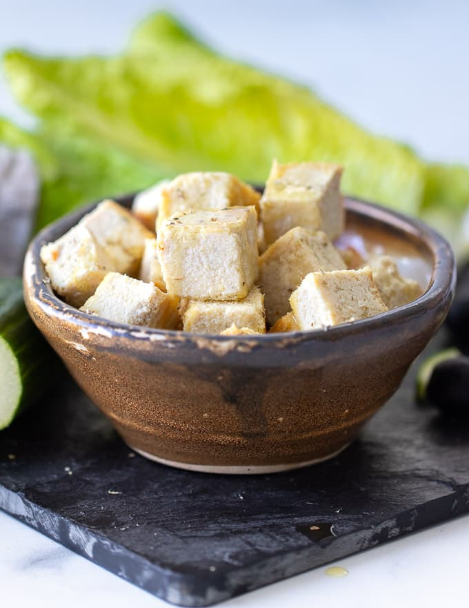 Vegan feta cheese made from tofu stacked in a bowl with a lettace leaf in the background.