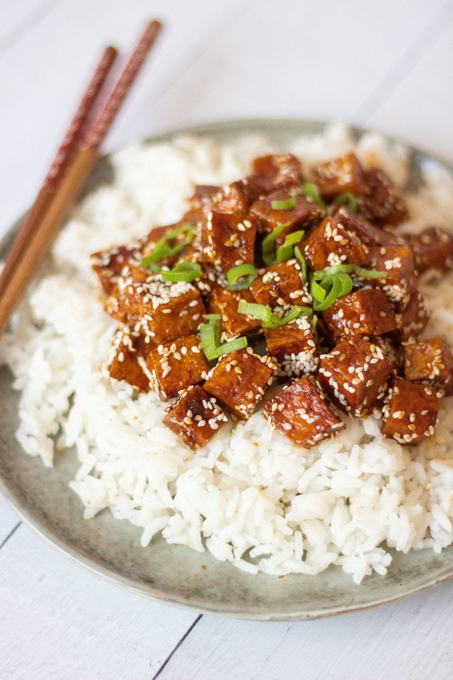 Garic tofu with seseme seeds sits on top of a plate of white rice. Topped with finely sliced spring onions the chopsticks sit on the side.