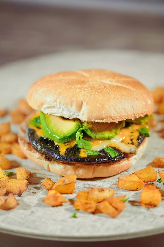 A vegan portobello mushroom burger sat on a textured wooden surface surrounded by sweet potatoes.