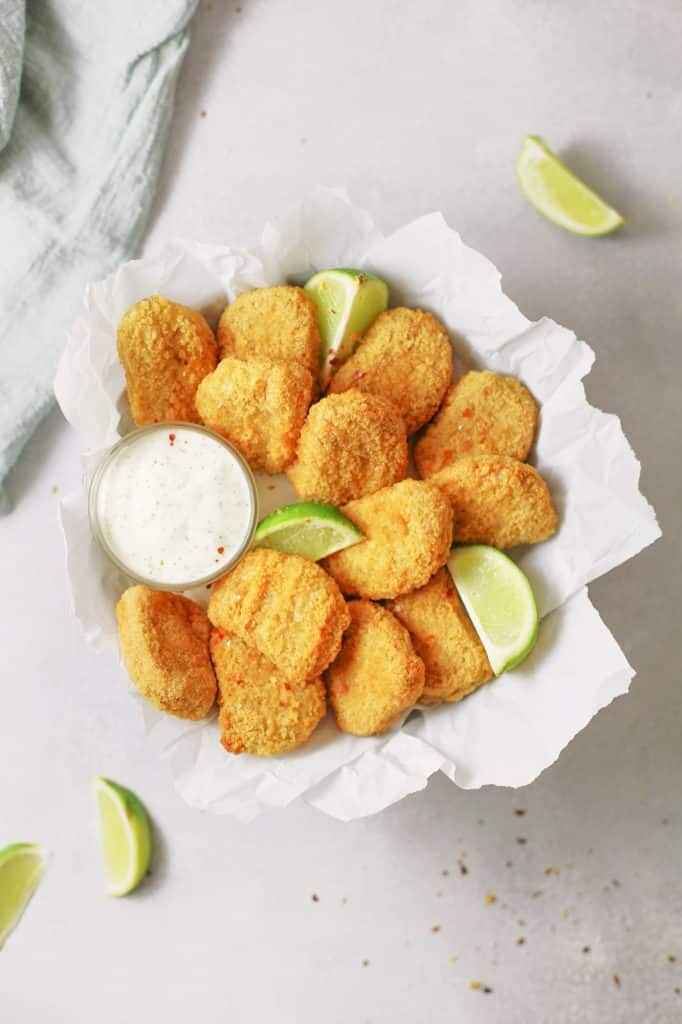 Tofu baked nuggets covered in bed crumbs served on a white table with a side of lemon and a side of dipping sauce.