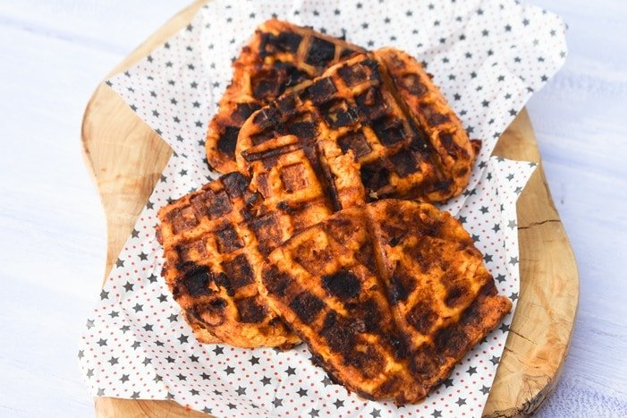 Three waffles sit on sheets of baking paper ontop of a chopping board.