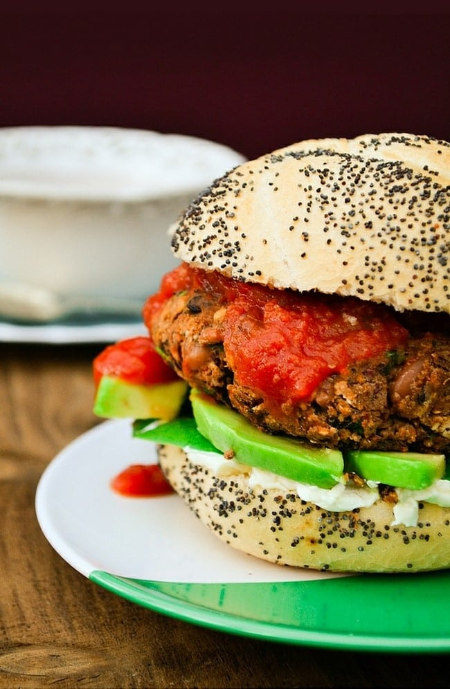 Spicy vegan burger inside a seseme seed coated bun on a white and green plate.