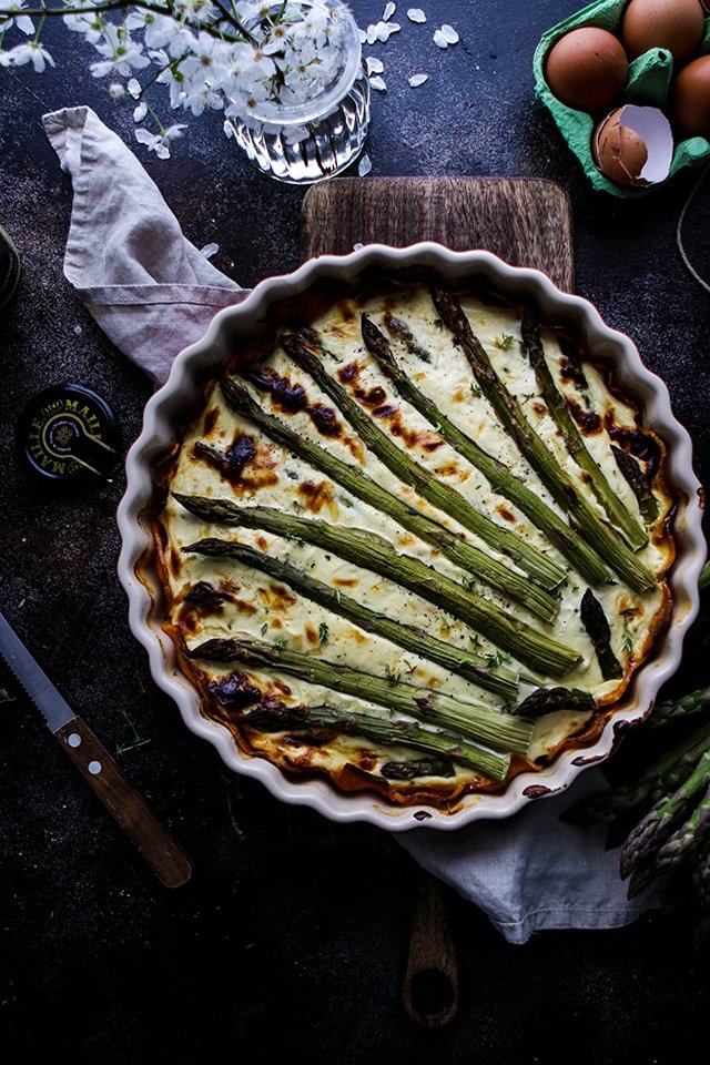 An entire Asparagus Quiche with Sweet Potato Crust sits inside a pie dish on a chopping board with a dark black background. At the side there's some cracked eggs, a decorative flower and a napkin.