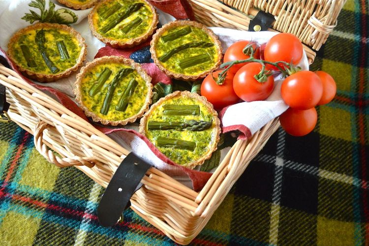 Five mini  Asparagus Tarts With A Pesto Surprise sit inside a wicker basket. At the side are some on the vine cherry tomatoes. The basket sits on a deocrative checked rug.