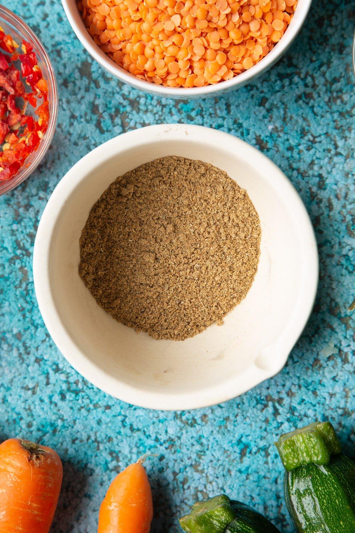 Ground spices in a mortar. Ingredients to make baked bean curry surround the mortar.