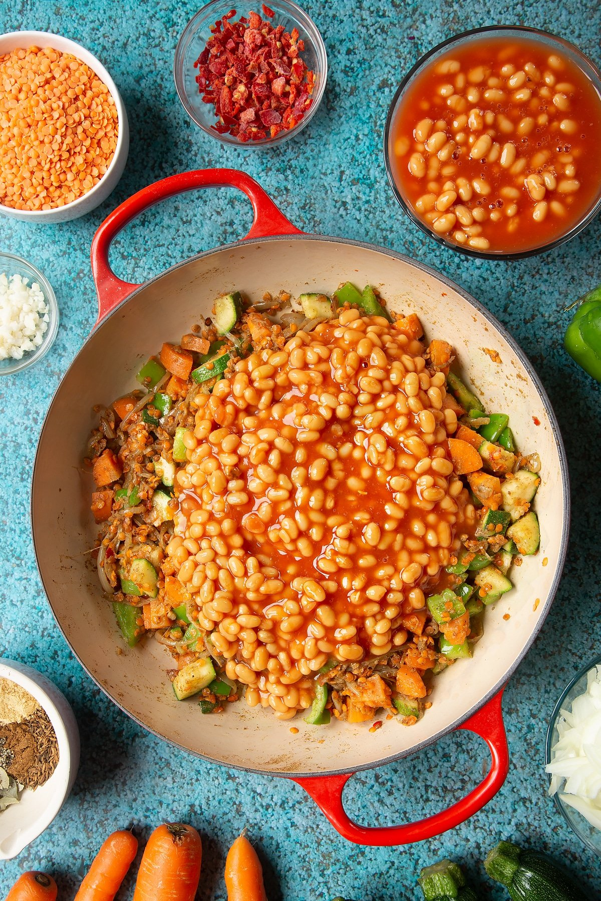 Fried onions, spices, peppers, carrots, courgette and red lentils in a pan with baked beans on top. Ingredients to make baked bean curry surround the pen.