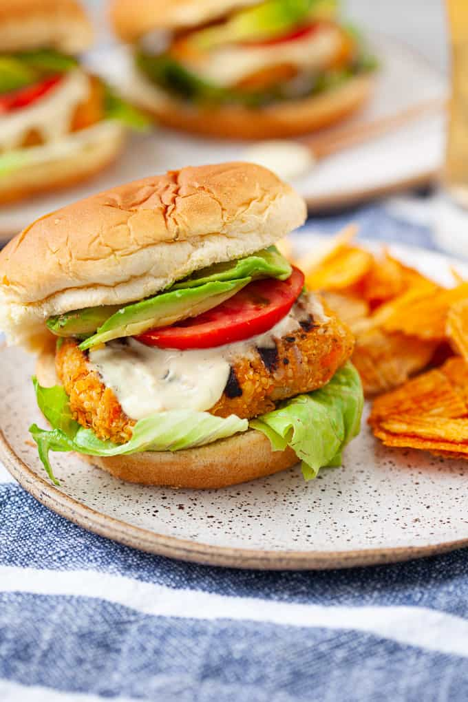 Buffalo chickpea burger on a decorative plate with a side of crisps. Two additional burgers are out of focus in the background.