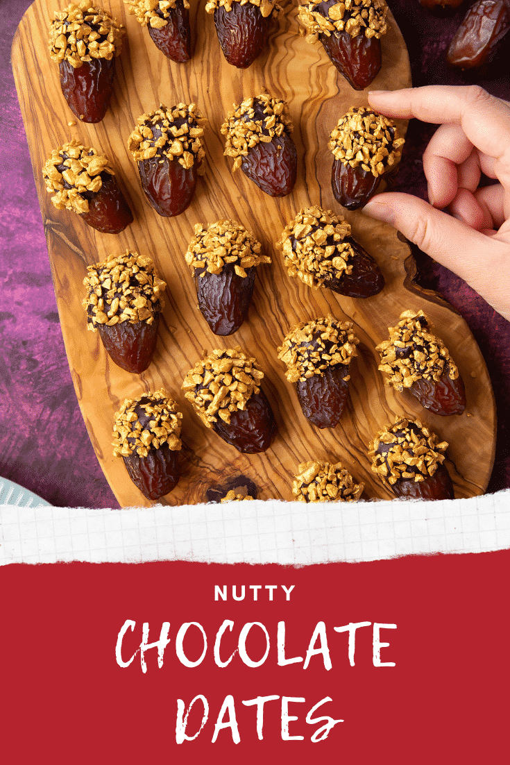 Medjool dates on a wooden board and. They have been dipped in chocolate and studded with gold chopped nuts. A hand reaches for one. Caption reads: nutty chocolate dates