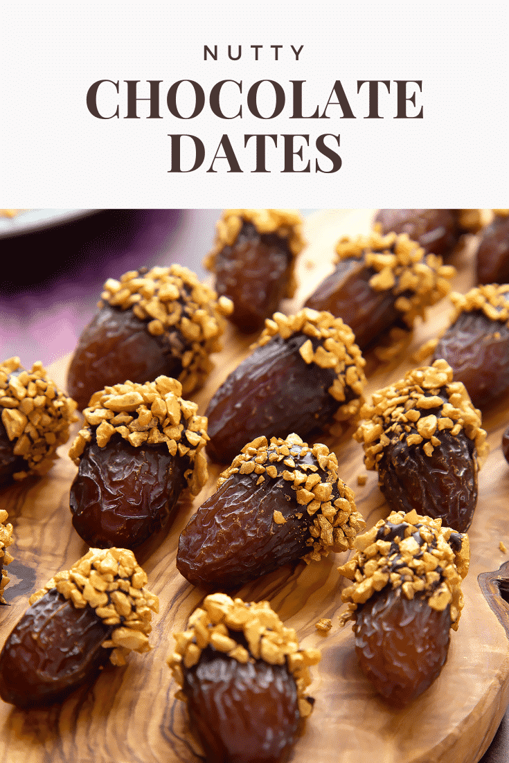 Medjool dates on a wooden board and. They have been dipped in chocolate and studded with gold chopped nuts. Caption reads: nutty chocolate dates
