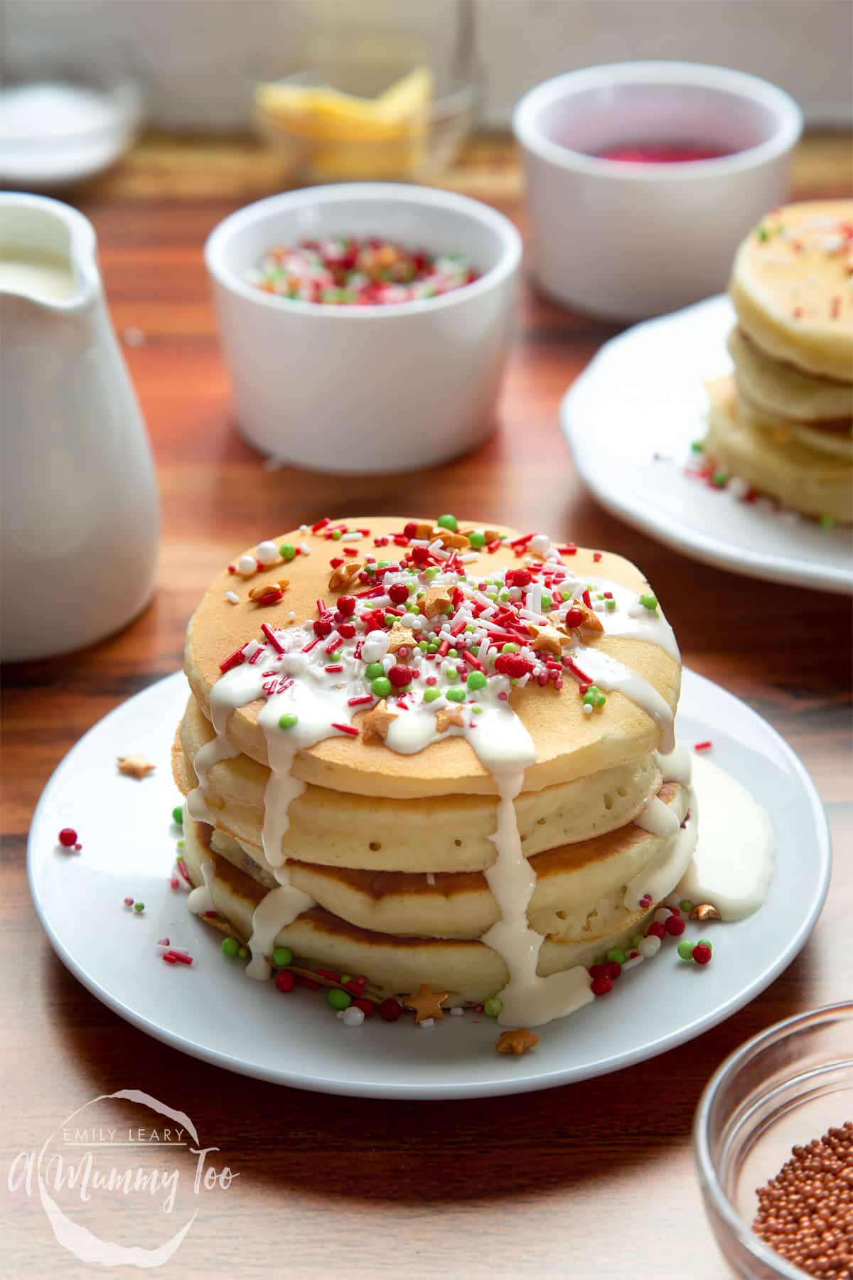 A tall stack of Christmas morning pancakes, stacked on a white plate, scattered with festive sprinkles and drizzled with cream.