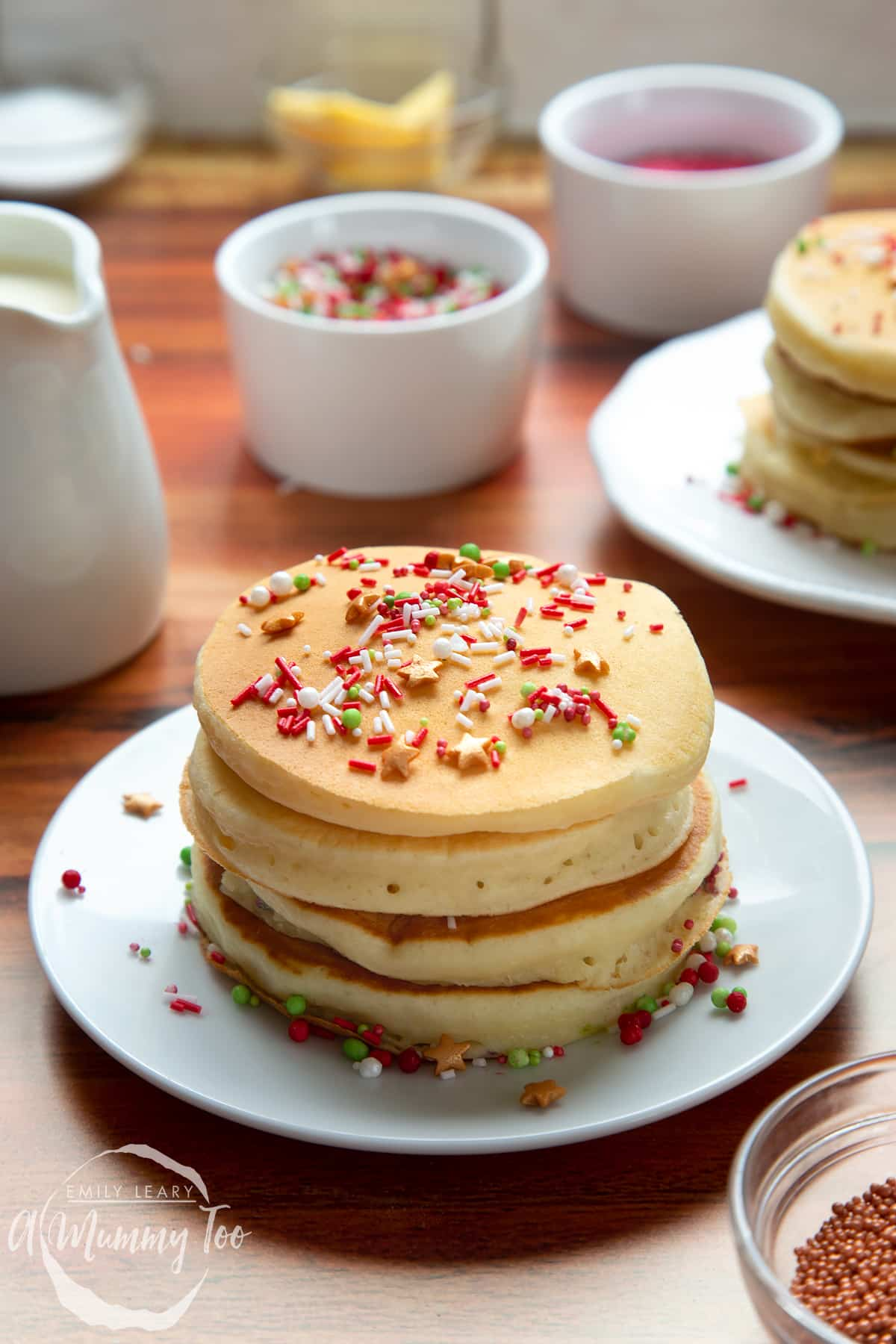 A tall stack of Christmas morning pancakes, stacked on a white plate, scattered with festive sprinkles.