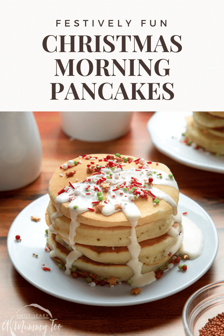 A tall stack pancakes, stacked on a white plate, scattered with festive sprinkles and drizzled with cream. Caption reads: festively fun Christmas morning pancakes