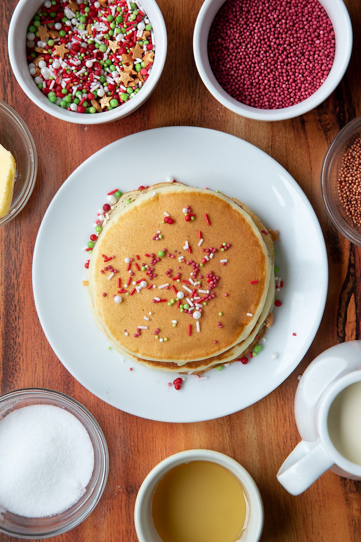 Two Christmas morning pancakes, stacked on a white plate, scattered with festive sprinkles.