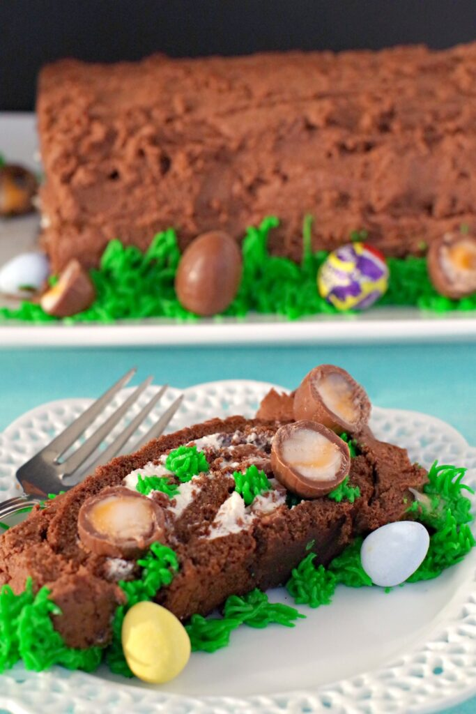 A slice of the easter egg chocolate roll sits on a white decorative plate covered in candy eggs and cadbury's cream eggs. In the background you can see the entire roll which sits on a white rectangular plate with a blue table cloth.