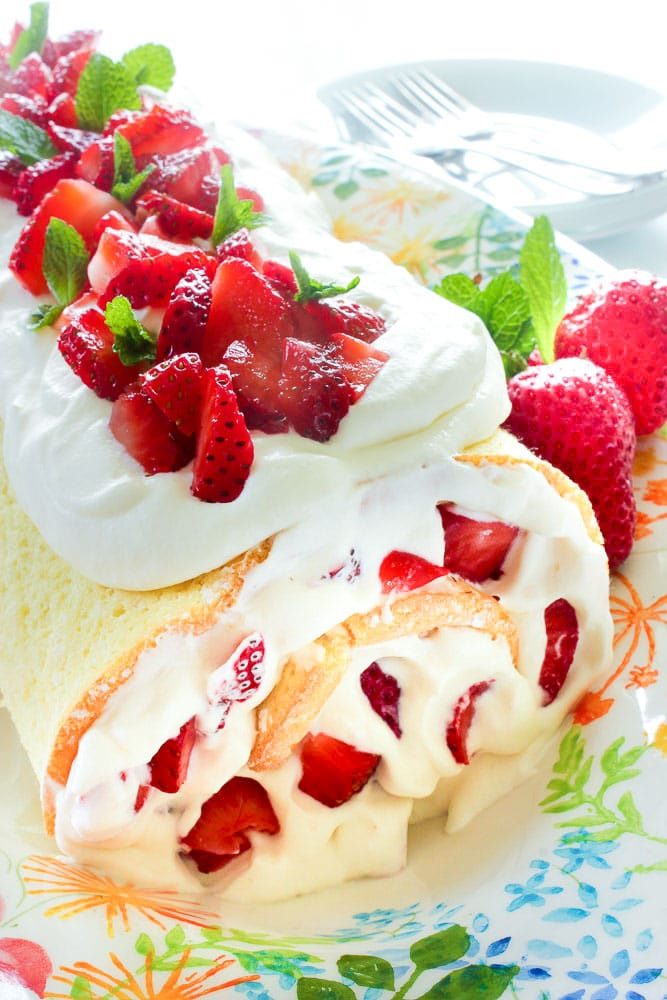 Strawberry Swiss roll decorated with chopped strawberries on a decorative white plate.