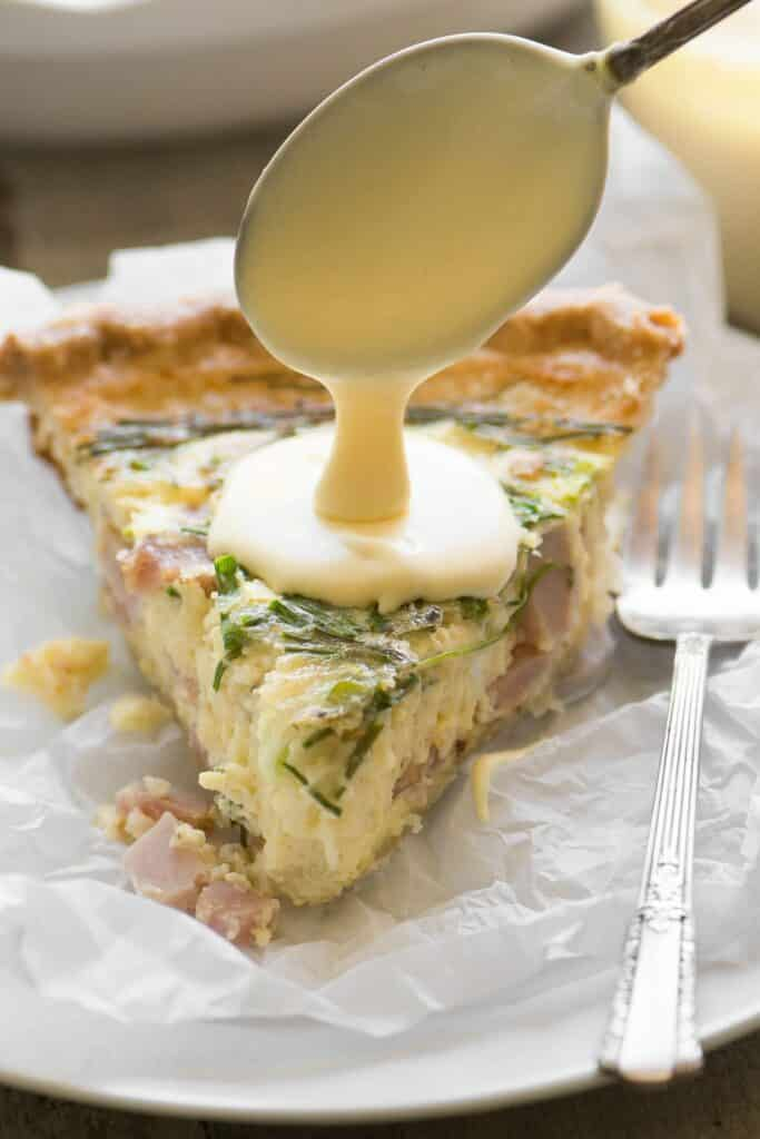 A slice of Eggs Benedict Quiche being drizzled in hollandaise sauce. A deocrative fork sits at the side.