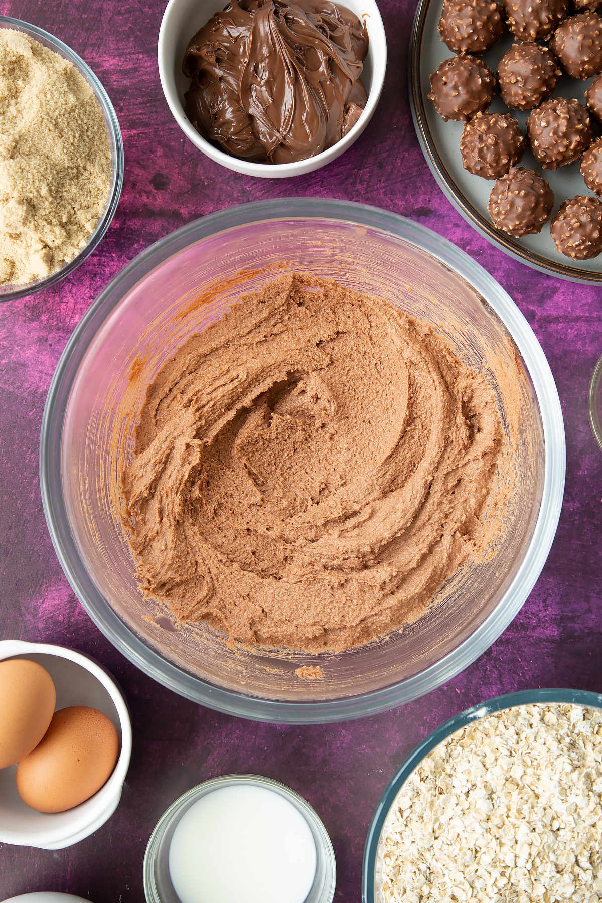Soft brown sugar, Nutella and butter beaten together in a large mixing bowl. Ingredients to make Ferrero Rocher cookies surround the bowl.