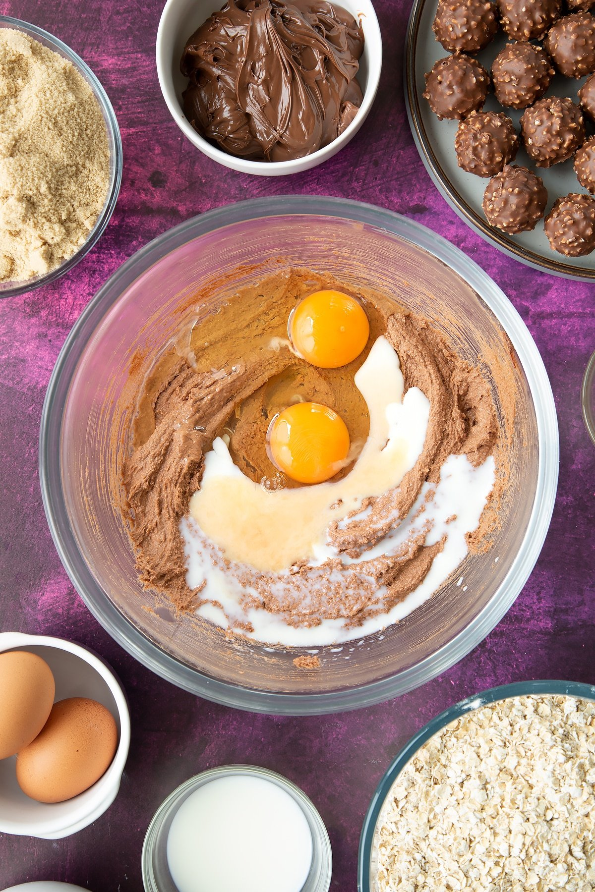 Soft brown sugar, Nutella and butter beaten together in a large mixing bowl with eggs and milk on top. Ingredients to make Ferrero Rocher cookies surround the bowl.