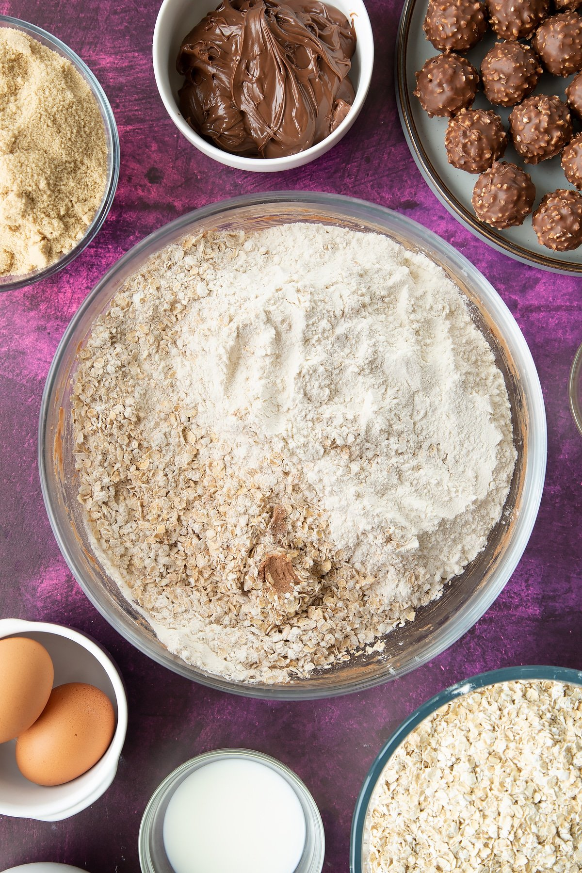 Soft brown sugar, Nutella, butter, eggs and milk beaten together in a large mixing bowl with flour and oats on top. Ingredients to make Ferrero Rocher cookies surround the bowl.