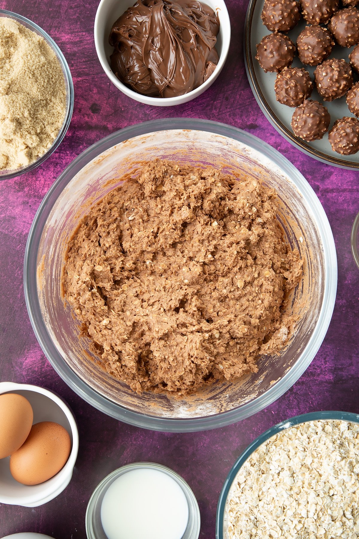 Oaty chocolate cookie dough a large mixing bowl with flour and oats on top. Ingredients to make Ferrero Rocher cookies surround the bowl.