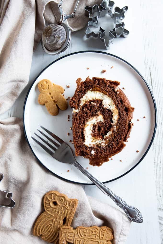 A slice of gingerbread chcolate log on a white plate. At the side is a minitiure gingerbread man and a decorative fork. The plate sits on a white wooden background with a table cloth at the side. At the top of the image there's a cute cookie cutter.