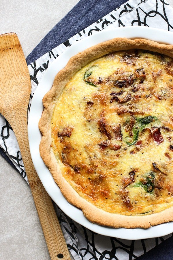 Bacon Spinach & Cheddar Quiche on a white plate. At the side is a wooden spatchular. Under the plate are two napkins a blue one and a white and black one.
