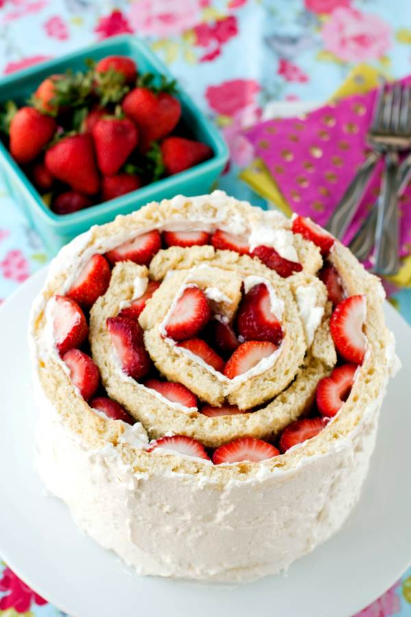 A strawberry shortcake roll-up cake sits on a white round plate. At the side there's a bowl of strawberries and some forks sitting ontop of some colourful decorative napkins.
