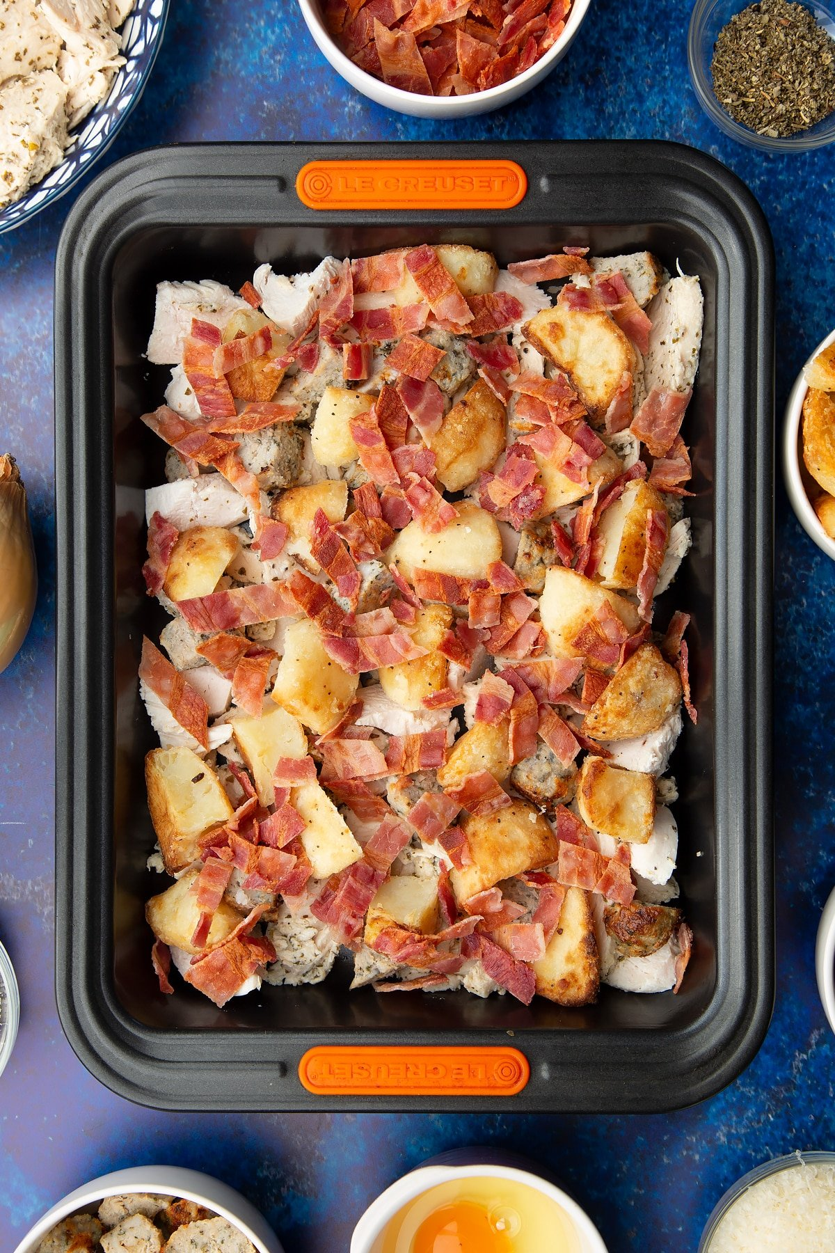 Chopped cooked turkey, stuffing, bacon and roast potatoes in a roasting dish. Ingredients to make a leftover Christmas dinner pie surround the tray.