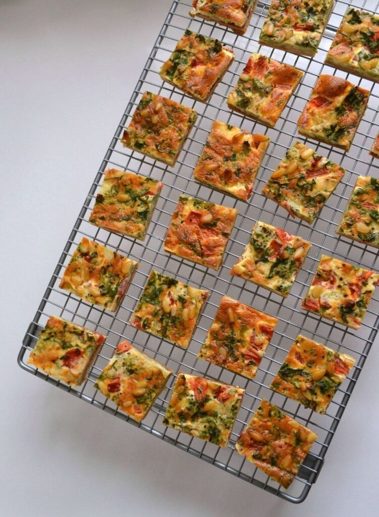 Mini quiche bites laid out in squares on a wire rack on a plain white background.