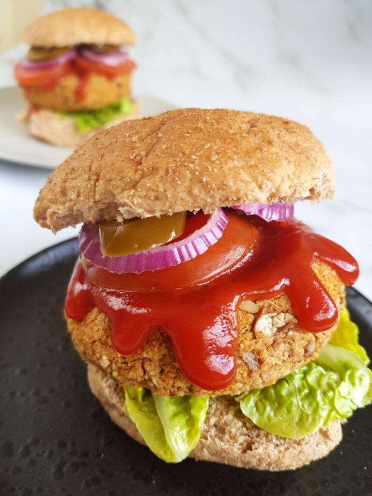 Pinto Bean Burgers with onions, tomatoes and ketchup on show. The burger is sat on a black plate on a white surface. In the background you can see another burger on a white plate.
