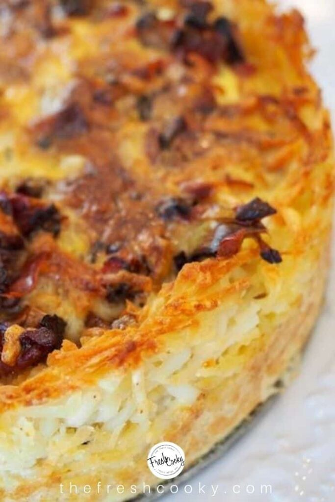 A close up of Prosciutto & Gruyere Quiche With Hash Brown Crust on a white background.
