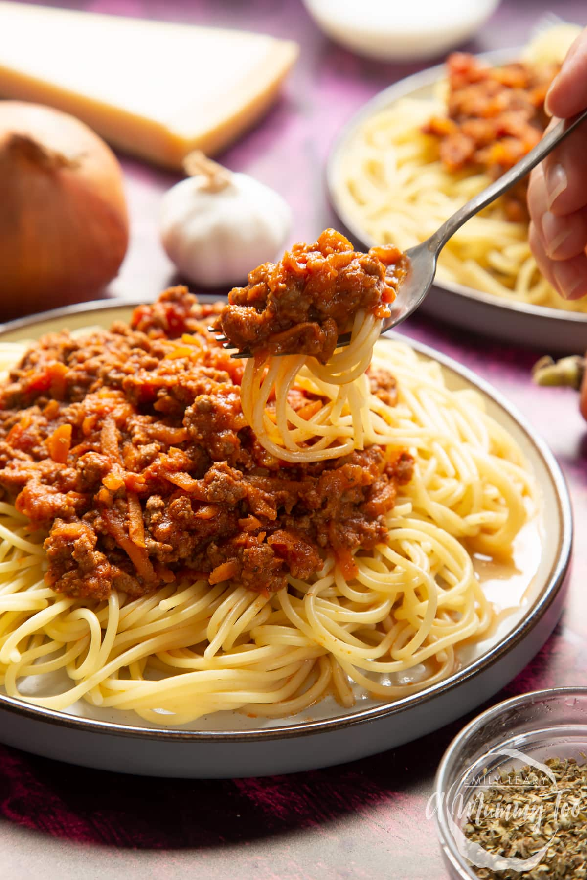 Side view of spaghetti bolognese Gordon Ramsay style served on plates. A hand holds a fork lifting spaghetti from the plate.