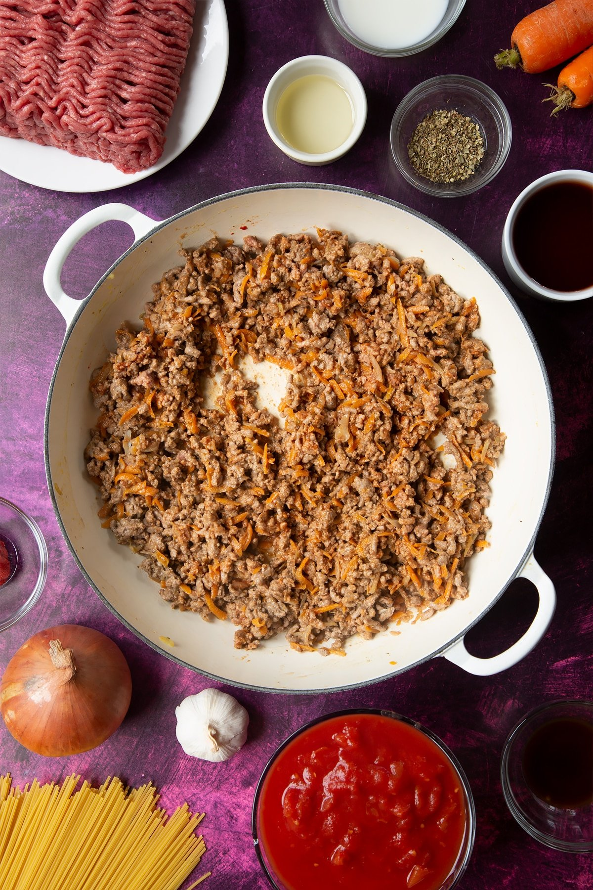 A large frying pan with fried carrot, onion, garlic, dried oregano, lean beef mince and tomato puree. Ingredients to make spaghetti bolognese Gordon Ramsay style surround the pan.