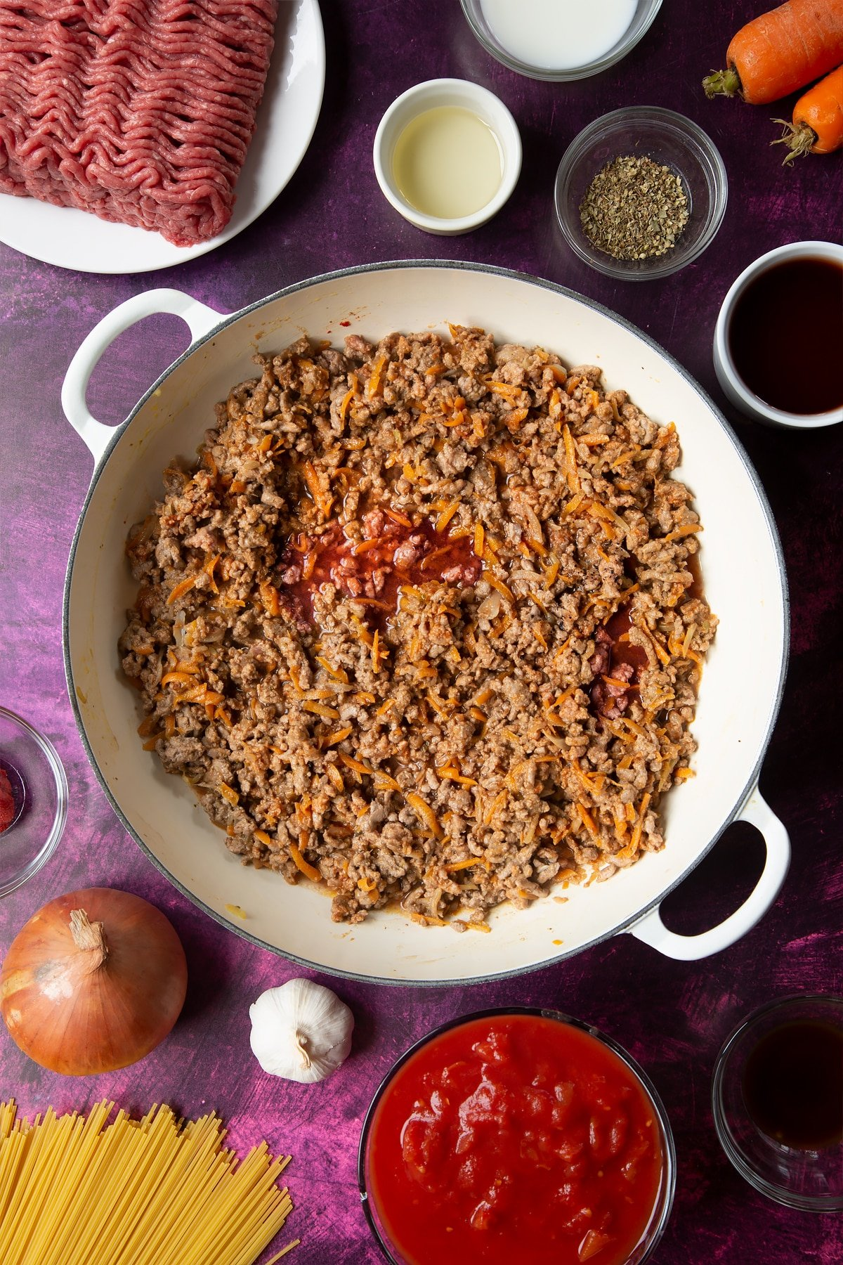 A large frying pan with fried carrot, onion, garlic, dried oregano, lean beef mince, tomato puree and red wine. Ingredients to make spaghetti bolognese Gordon Ramsay style surround the pan.