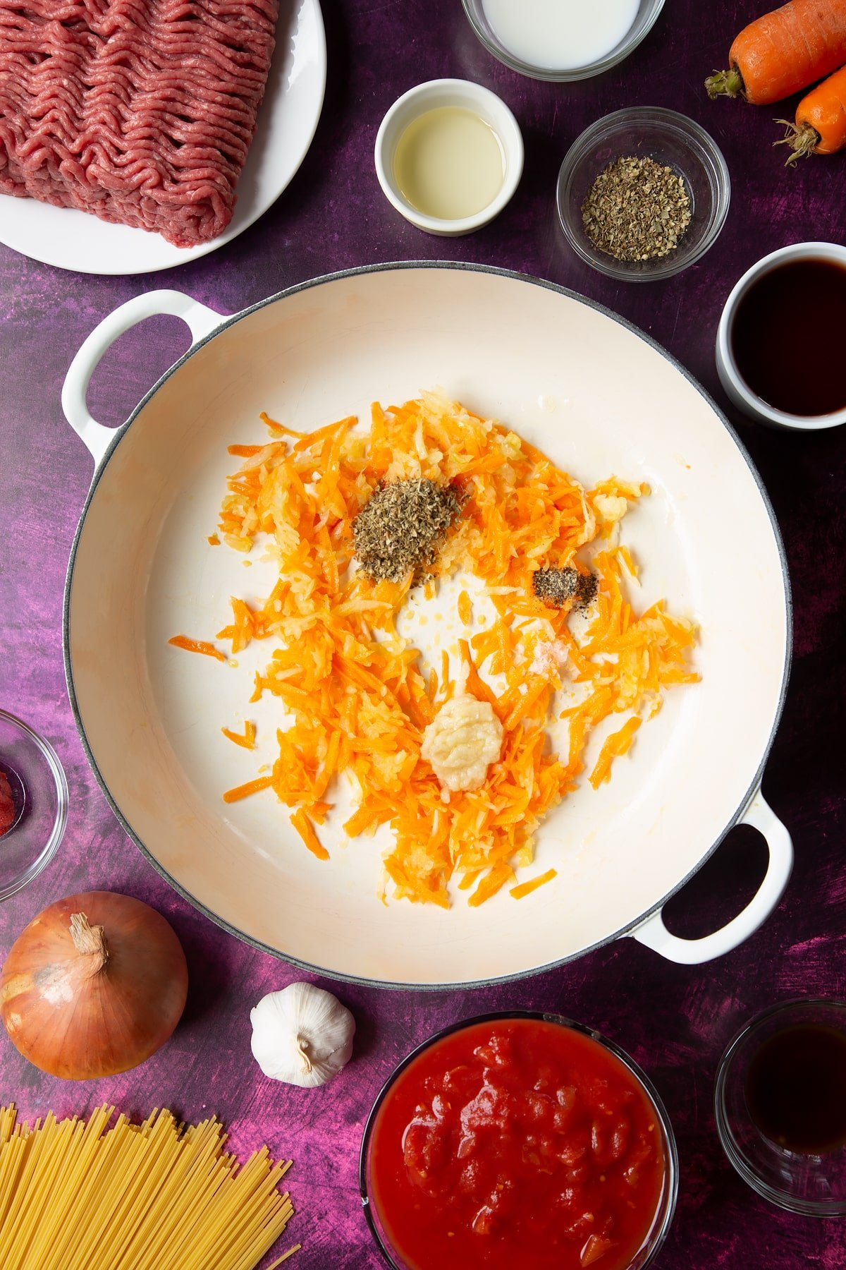 A large frying pan with fried carrot and onion, plus minced garlic and dried oregano. Ingredients to make spaghetti bolognese Gordon Ramsay style surround the pan.